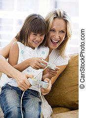 Woman and young girl in living room with video game...