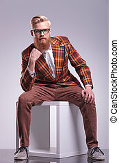 seated fashion man with beard and glasses looking pensive at...