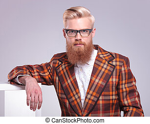 fashion man with long red beard and glasses resting in...