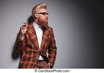 side view of a cool fashion man with great hairstyle smoking...