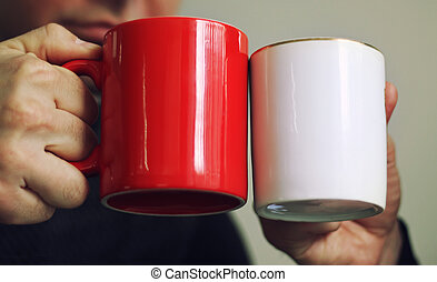 Two cups, red and white - Two men are holding red and white...