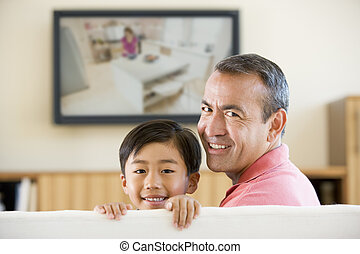 Man and young boy in living room with flat screen television...
