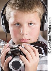 Young boy wearing headphones in bedroom holding many...