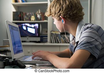 Young boy in bedroom using laptop and listening to MP3...