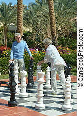 Senior couple playing street chess