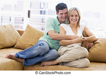 Couple in living room with remote control smiling