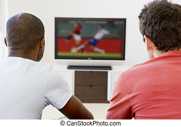 Two men in living room watching television