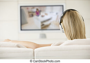 Woman in living room watching television and wearing...
