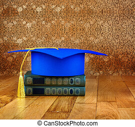 Graduation mortarboard on top of stack of books on a wooden table on background of vintage wall