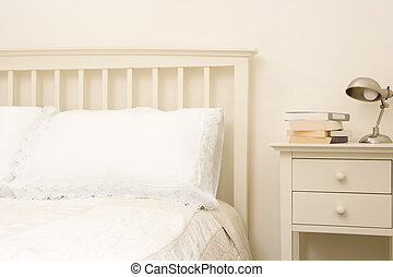 Empty bedroom with books on nightstand