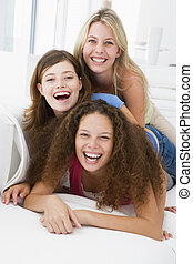 Three women in living room playing and smiling
