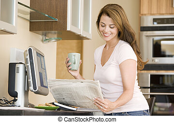 Woman in kitchen at computer with newspaper and coffee...