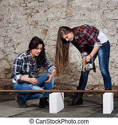 Two long-haired young woman with an angle grinder