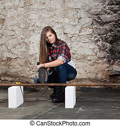Young long-haired woman with an angle grinder