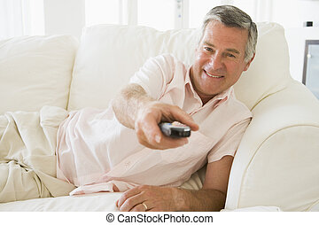 Man in living room using remote control smiling