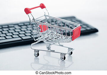 Shopping cart and keyboard on light background