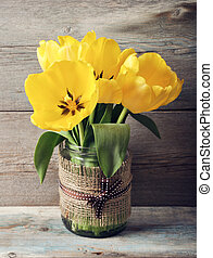 Beautiful tulips bouquet in vase on wooden background