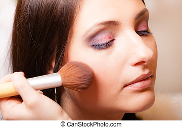 Makeup artist applying with brush powder rouge on female...