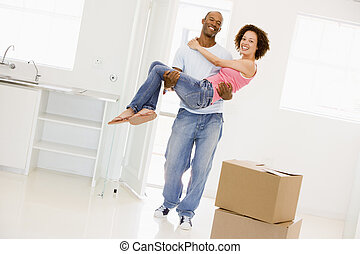 Husband holding wife in new home smiling