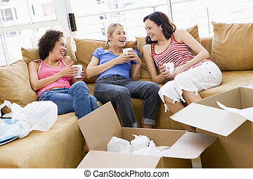 Three girl friends relaxing with coffee by boxes in new home...