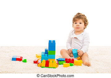 Toddler boy playing with building blocks and sitting on fur...