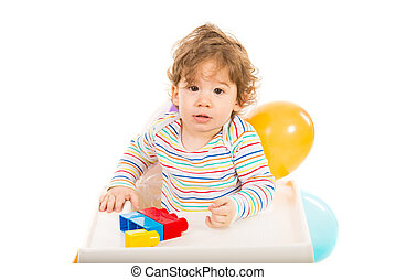 Toddler boy playing with building blocks and sitting in a...