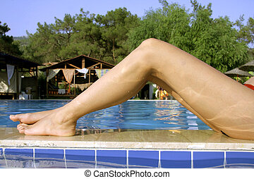 legs - womans beautiful thin legs alongside pool in summer