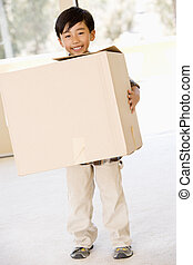 Young boy with box in new home smiling