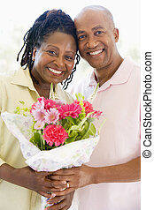 Husband and wife holding flowers smiling