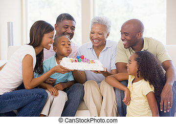 Family in living room smiling with young boy blowing out...