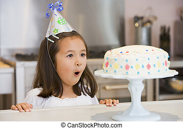 Young girl wearing party hat at kitchen counter looking at...