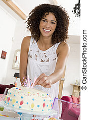 Woman putting candles in cake smiling