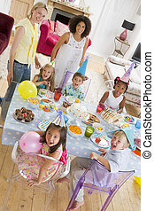 Young children at party with mothers sitting at table with...