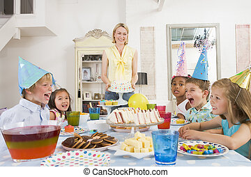 Young children at party sitting at table with mother...