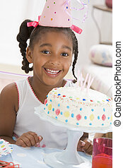 Young girl wearing party hat with cake in front of her...