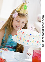 Young girl wearing party hat looking at birthday cake...