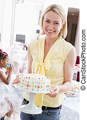 Woman at party holding birthday cake smiling