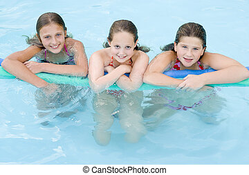Three young girl friends in swimming pool with pool noodle...
