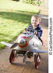 Young boy playing outdoors in airplane smiling