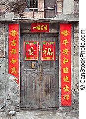 Old wooden Chinese door with peeling fortune posters