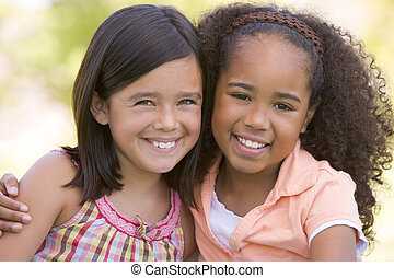 Two young girl friends sitting outdoors smiling