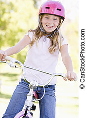 Young girl on bicycle outdoors smiling