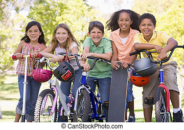 Five young friends with bicycles scooters and skateboard...