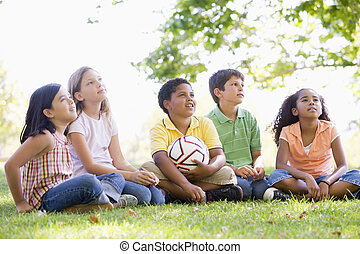Five young friends sitting outdoors with soccer ball looking up