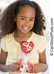 Young girl on Valentine\\\'s Day holding love themed balloon...