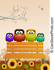 family of owls on the bench in spring