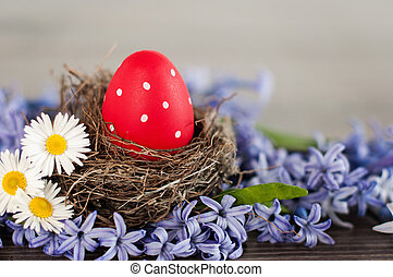 Red Easter egg in a nest among spring flowers