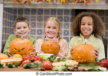 Three young friends on Halloween with jack o lanterns and...