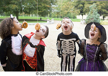 Four young friends on Halloween in costumes eating donuts hangin