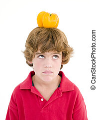 Young boy with yellow pepper on his head frowning